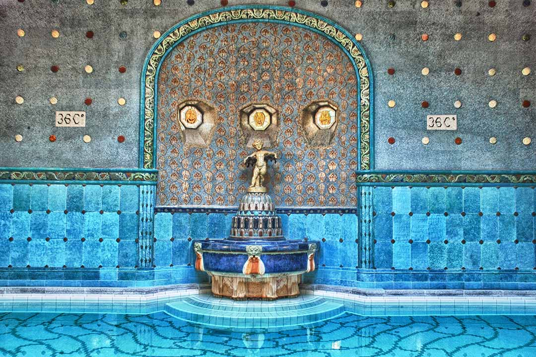 A fountain surrounded by bright blue and turquoise tiles in the Szechenyi Baths.