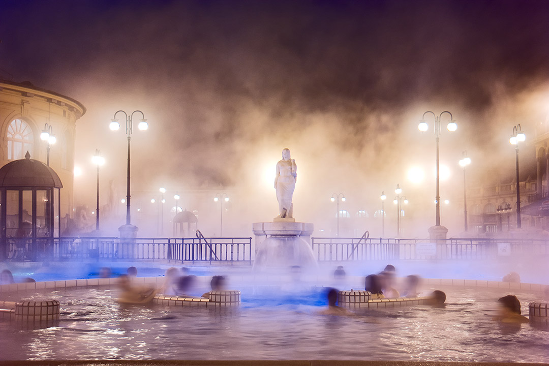 A view of people in the Szechenyi Baths at nighttime, with steam rising from the water.