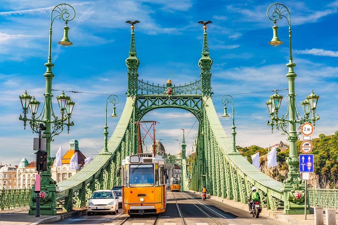 Liberty Bridge in Budapest, sunny daylight. A yellow tram is crossing the bridge.