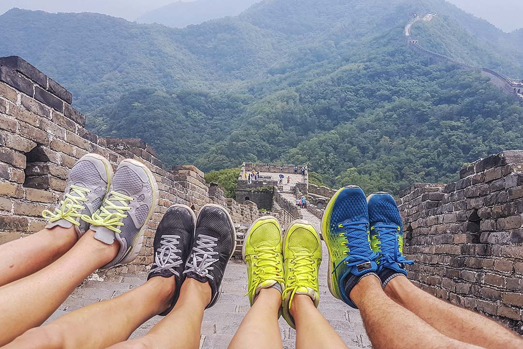 Four people sat down on the Great Wall of China with their walking trainers held proudly in the air