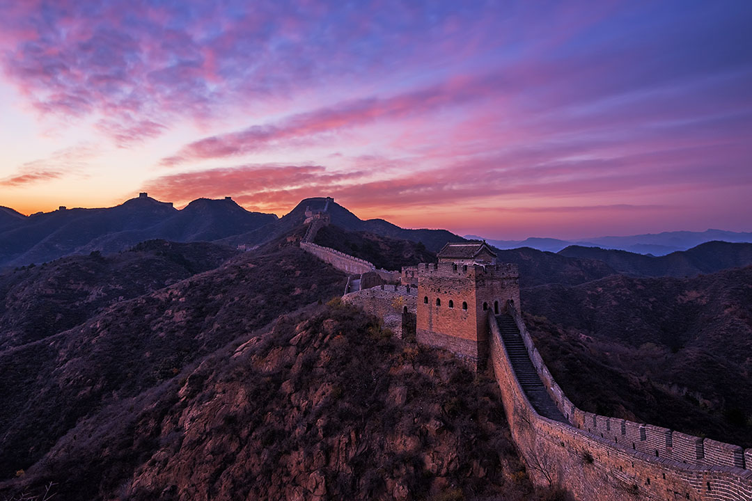 A purple sun set over a quiet section of the Great Wall of China