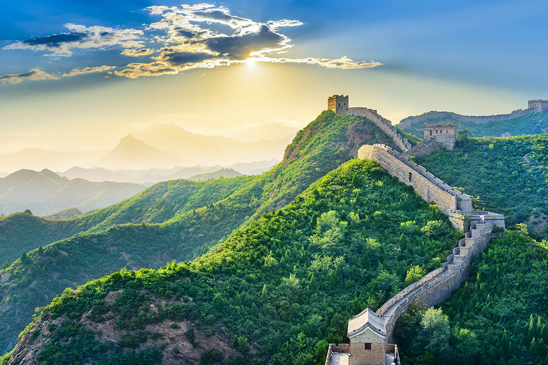 The Great Wall of China stretching into the distance with misty hills and a rising sun in the background