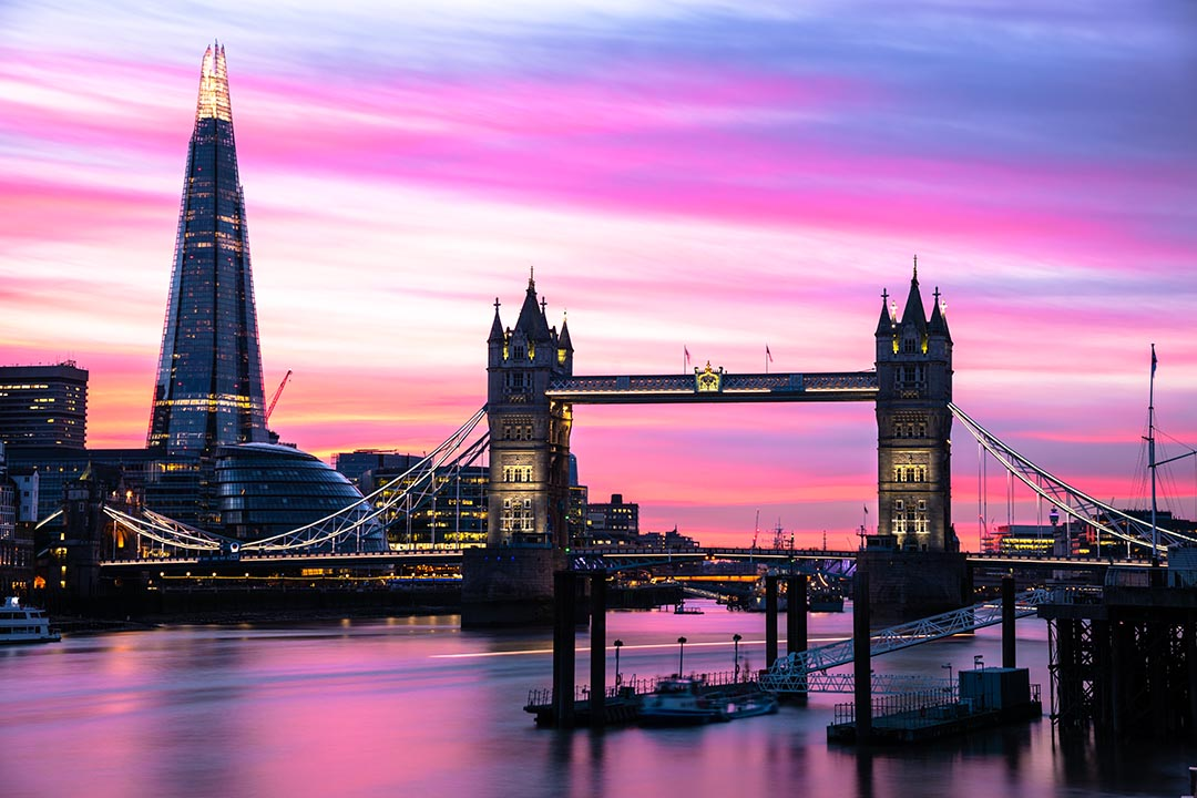 A view of Tower Bridge in the middle and The Shard on the left on the River Thames at dusk. The sky is a pink and purle hue which is reflecting in the water of the river.