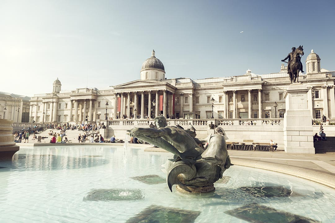 The fountain at Trafalgar Square with the National Portrait Gallery in the background on a clear day.