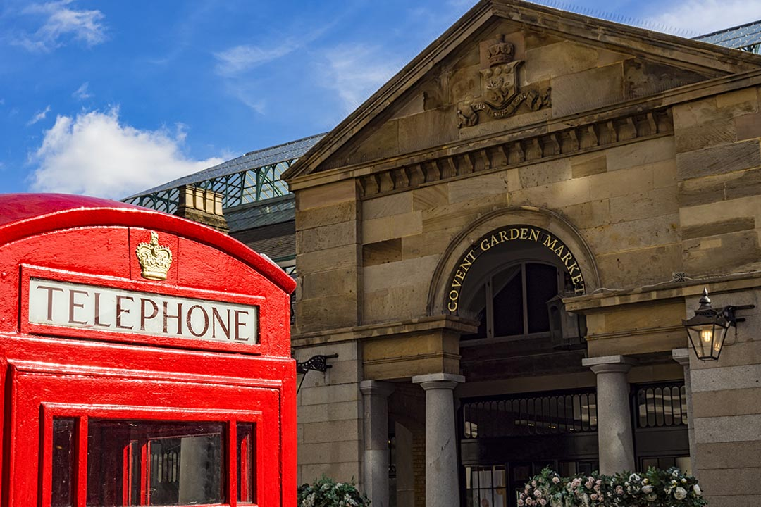 A red british telephone box with Covent Garden in the background.