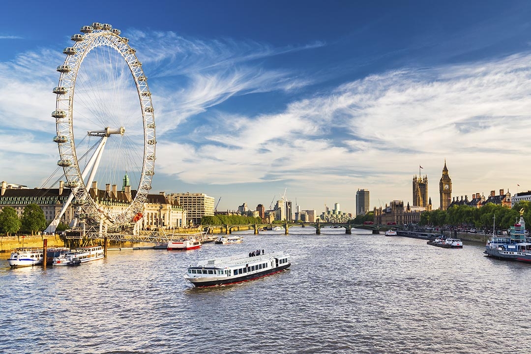 A view of the River Thames with a river cruising on the water. Big Ben and Westminster in on the right of the river and the London Eye is on the left on the River Thames.