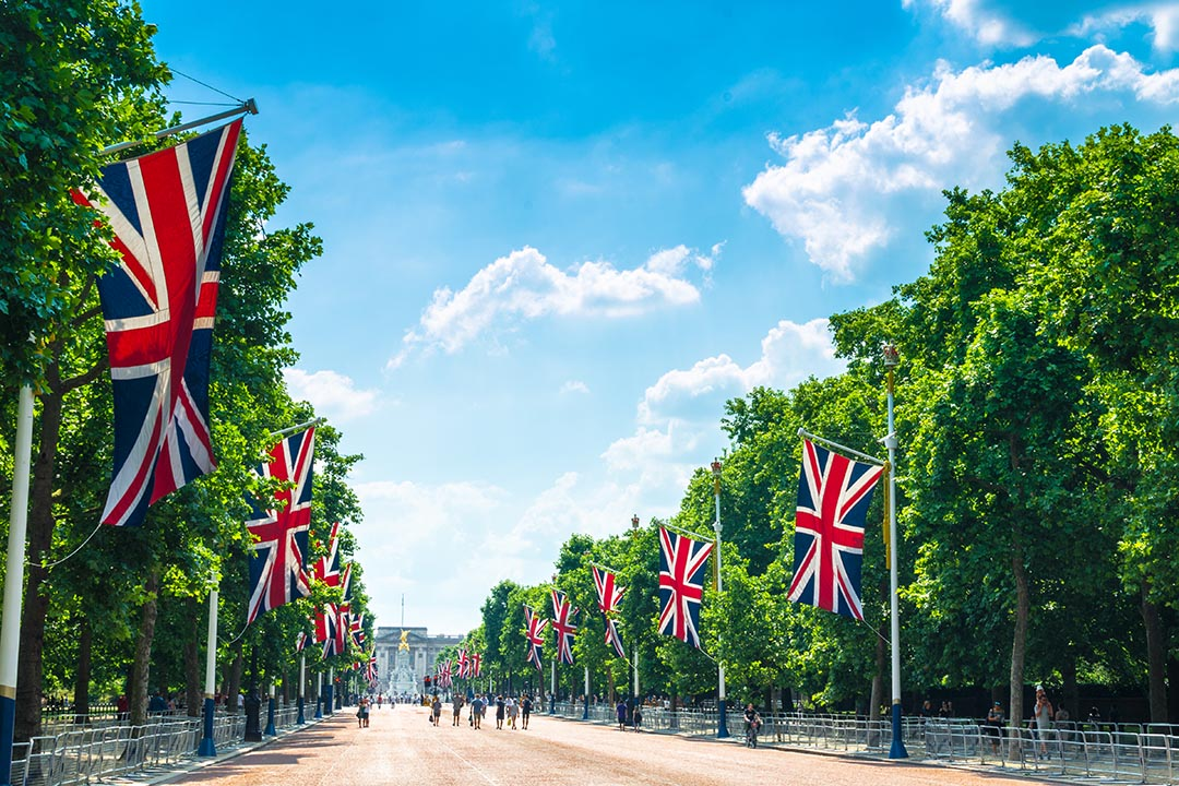 United Kingdom flags and green leafed trees line The Mall, the big road leading towards Buckingham Palace.