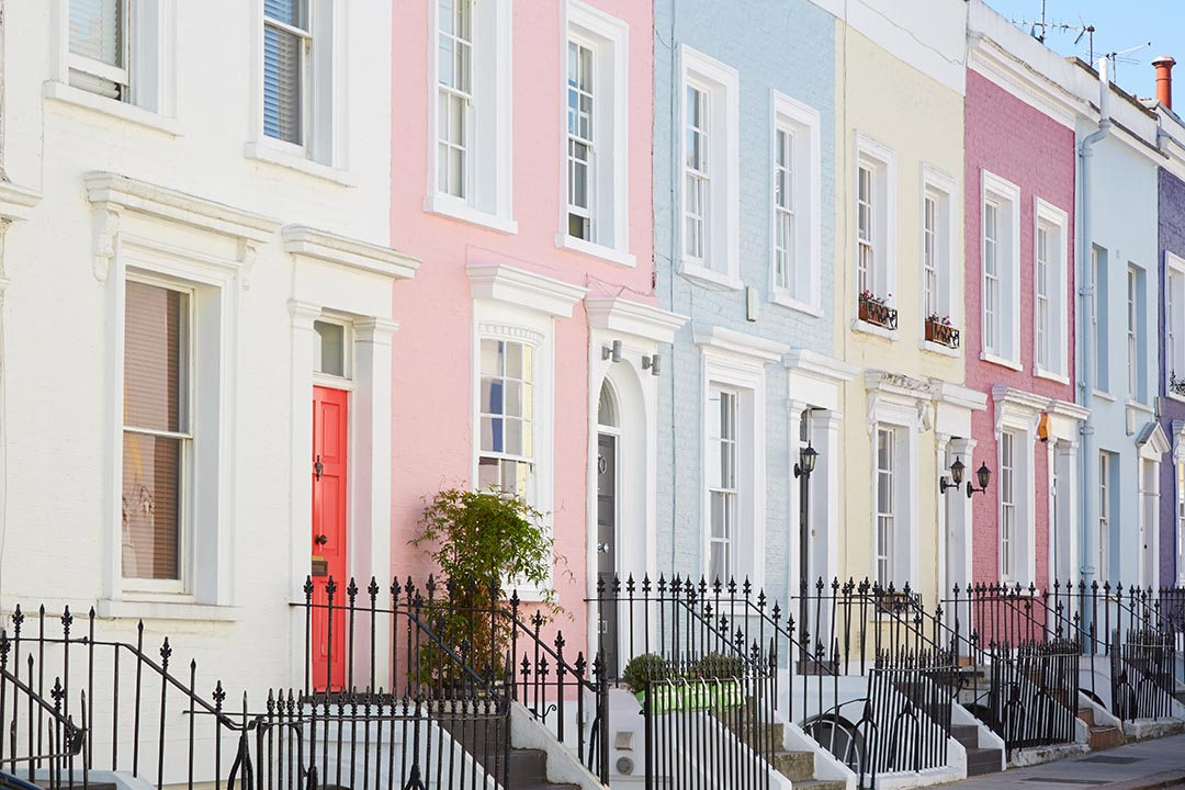 Colourful terrace houses in Notting Hill in London. Each individual house is painted pastel colours of cream, pink, blue and yellow.