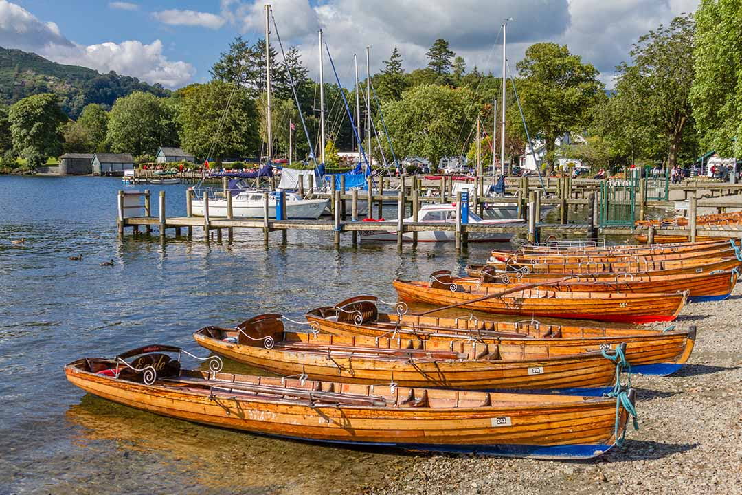 Wooden rowing boats moored on a pebble beach with a jetty in the back