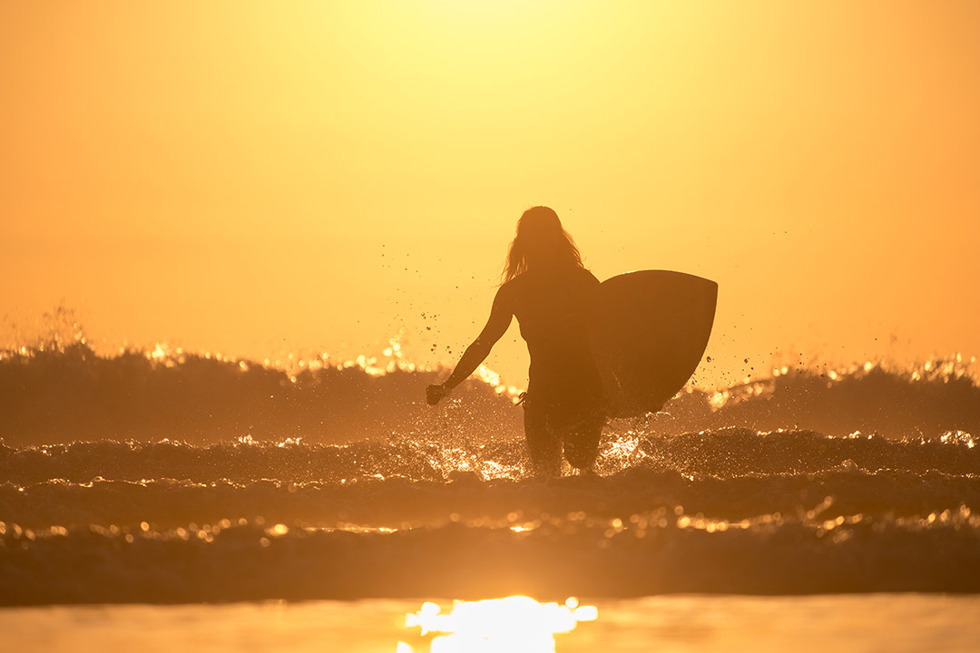 Woman with surfboard runs from the ocean with lots of splashes