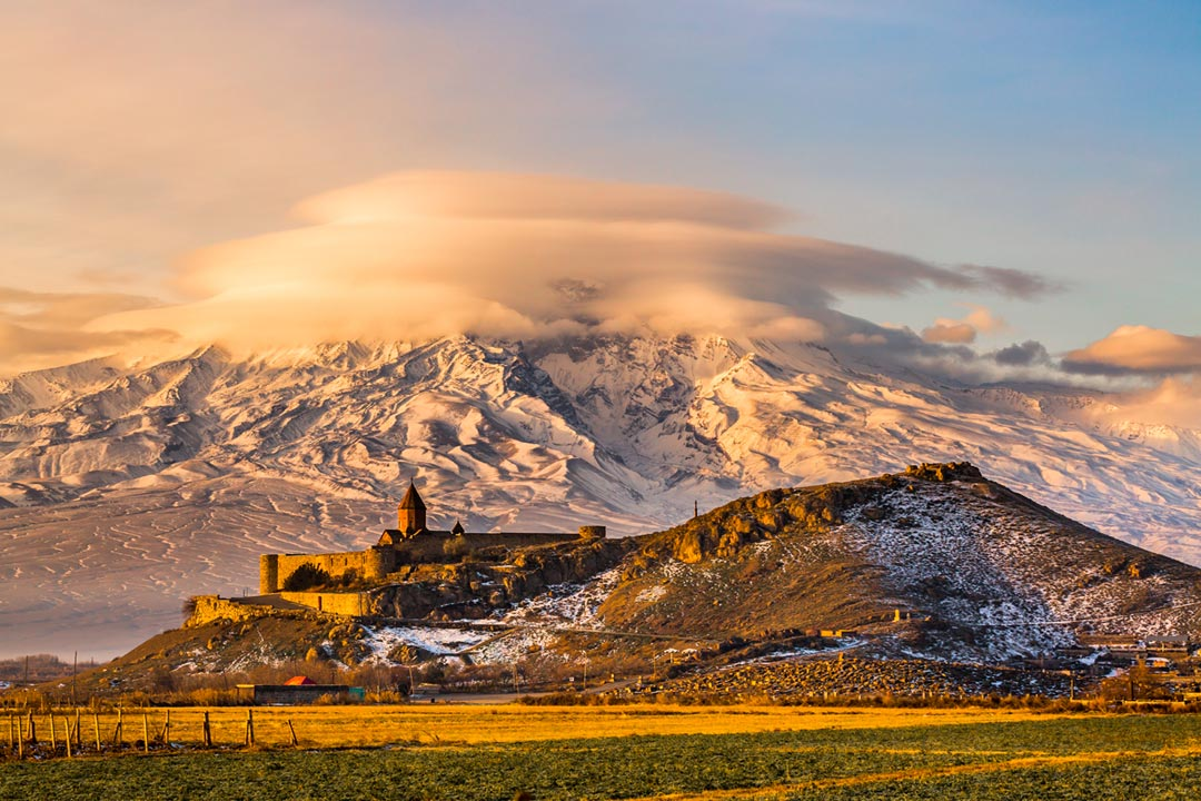 Snowy mountains shrouded by clouds. An ornate walled monastery sits on a hillside in the foreground