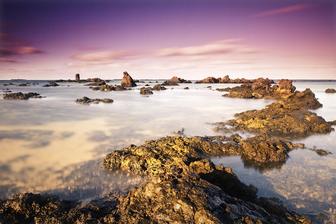 A purple sunset below a rocky cove