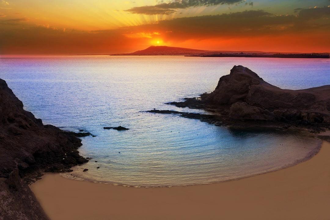 The sun setting on a beach cove by the sea