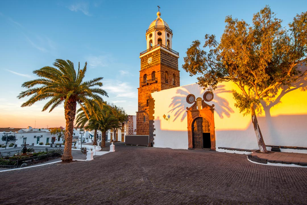 A yellow sunset glowing on the white stucco of a traditional church
