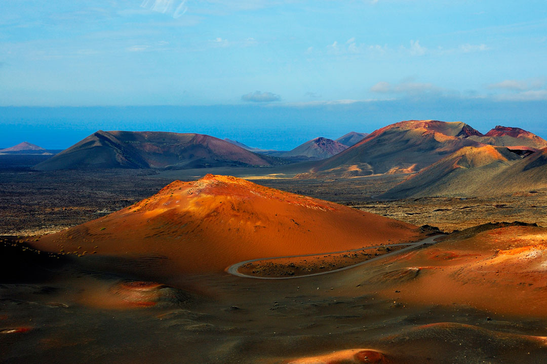 Red volcanic cones and craters leading to a blue sea