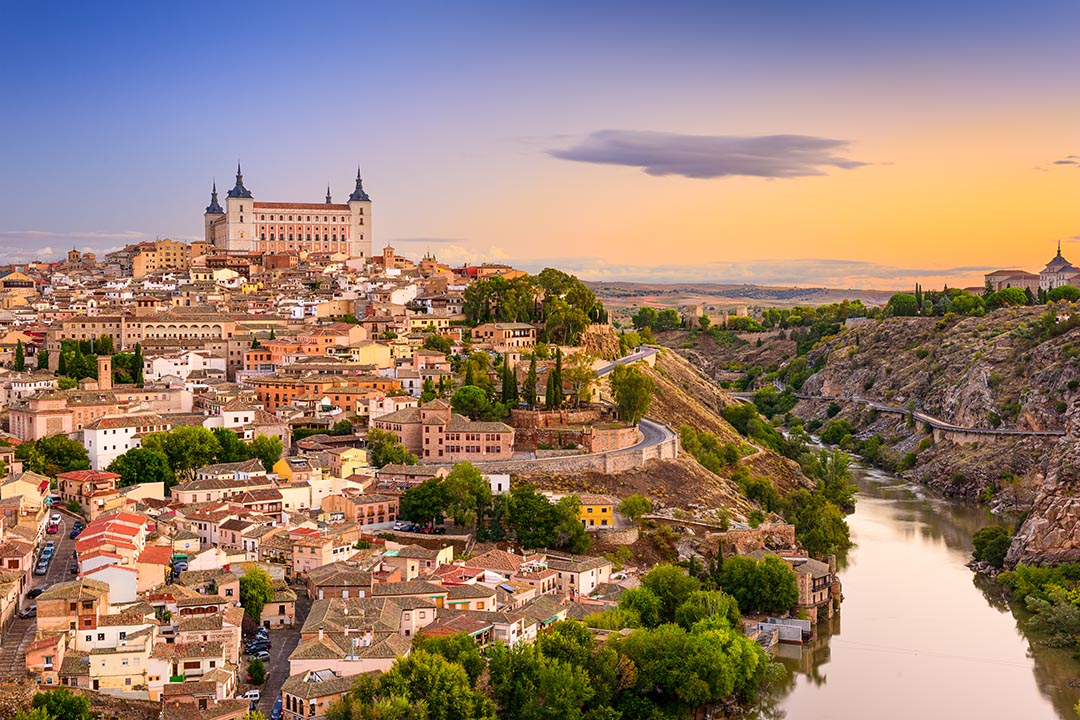 A landscape view of Toledo. The city is situated on a hill with terracotta roofs on the buildings. It slopes down the the Tagus River on the right of the image.