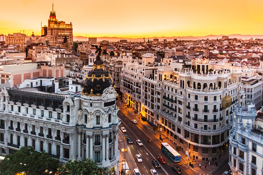 Panoramic aerial view of Gran Via, the main shopping street in Madrid at sunset as the sky is orange in the background and the buildings are twinkling with lights.