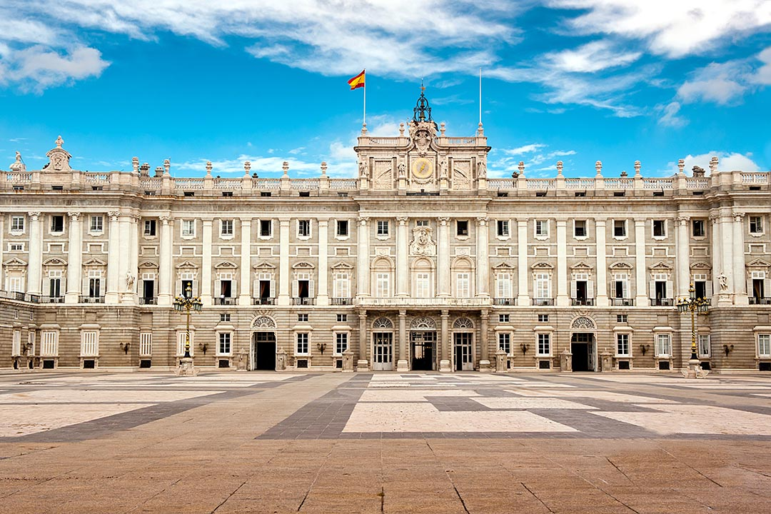 A front view of Palacio Real de Madrid - the Royal Palace of Madrid with blue skies in the background.