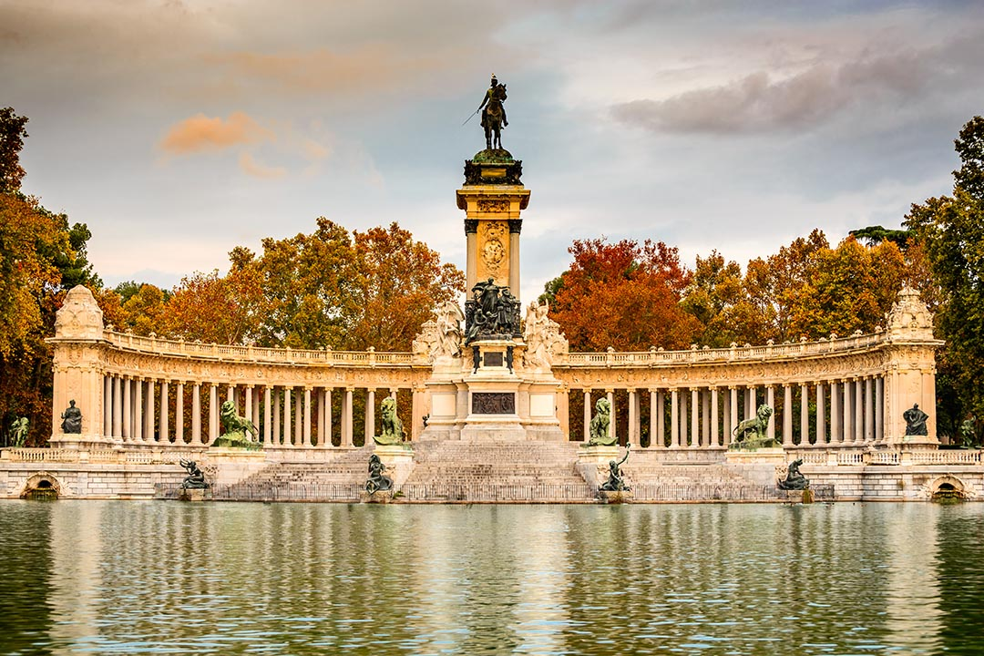 A landscapre view of Retiro Park with its lake and curved stone wall behind.