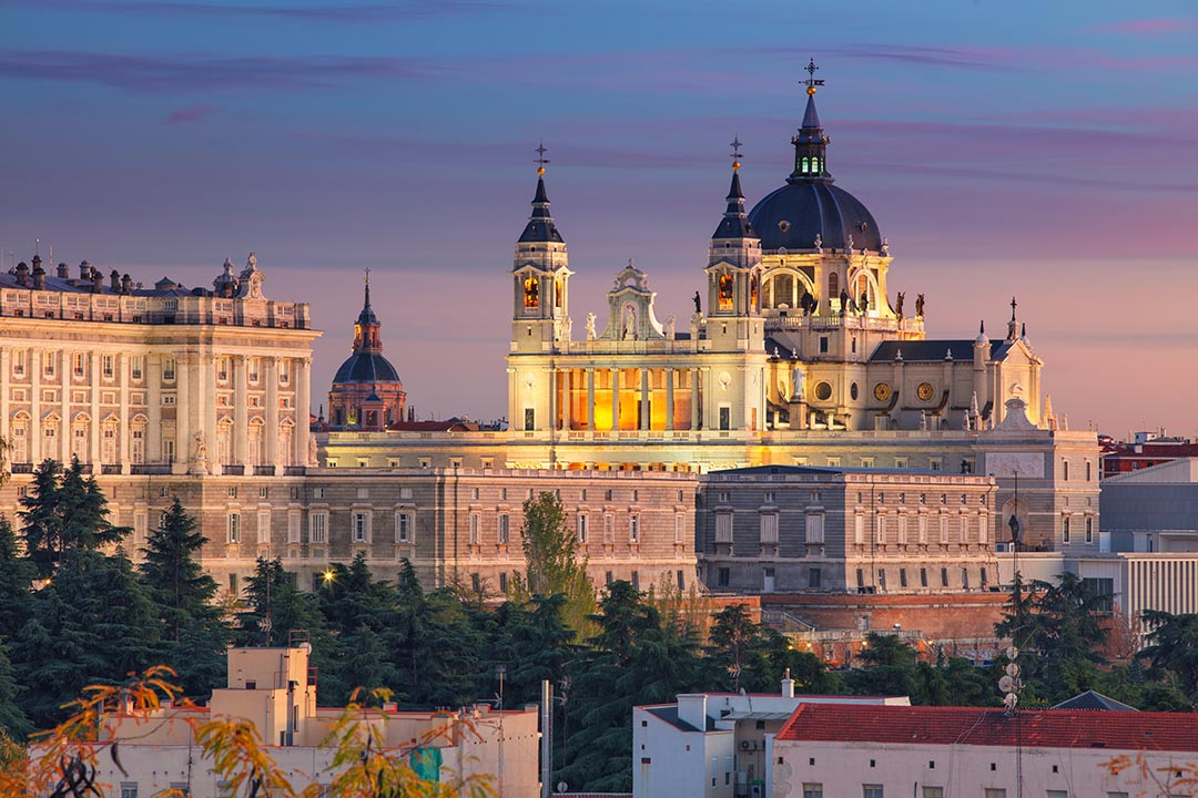 An image of Madrid's skyline with Santa Maria la Real de La Almudena lit up against a dusk sky and smaller buildings in the foreground.