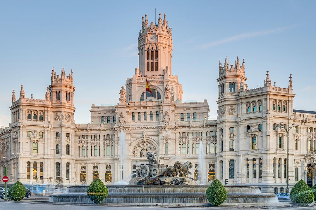Cibeles Fountain located downtown Madrid, Spain. This fountain is carved out of pale stone, has many windows and has two small trees in front of it.