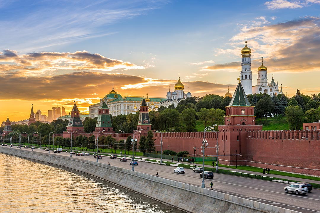 A view of Kremlin in Moscow over the river, with cars in the foreground