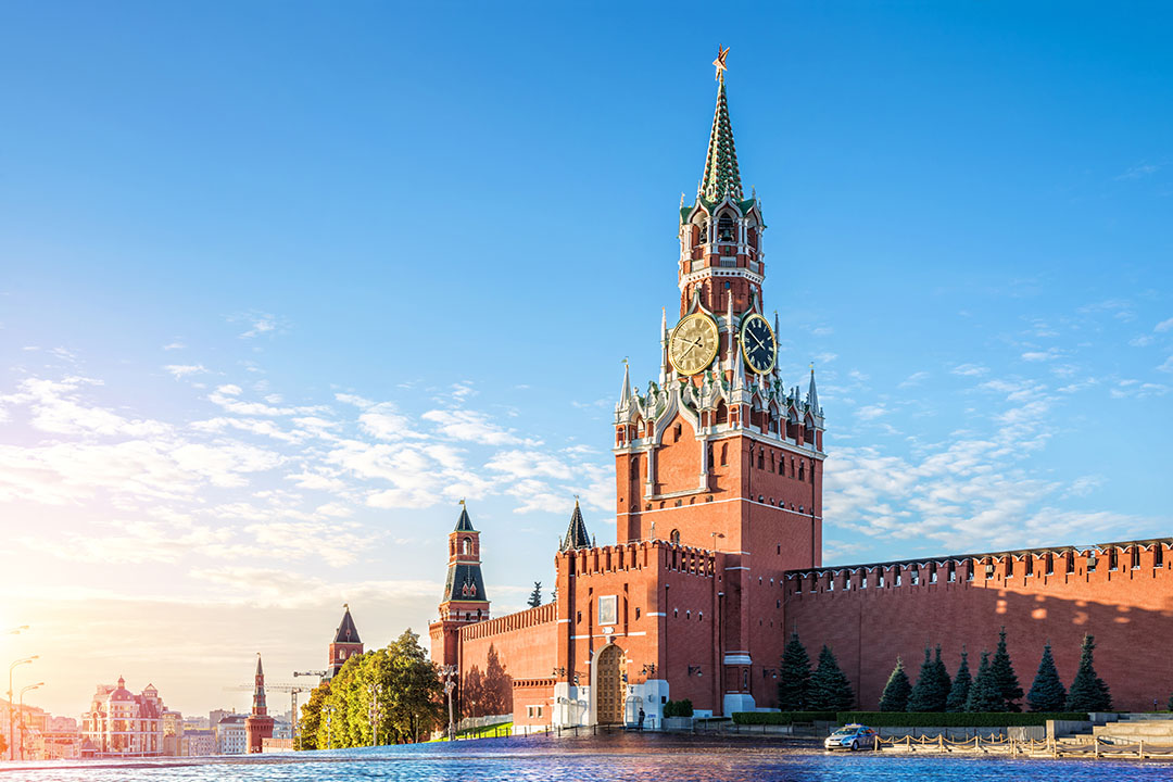 Spasskaya tower of the Kremlin stands next to a river bed.