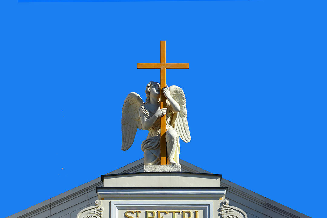 Angel statue with a cross, blue sky. Top of the Lutheran Church of Saint Peter and Saint Paul. Saint Petersburg