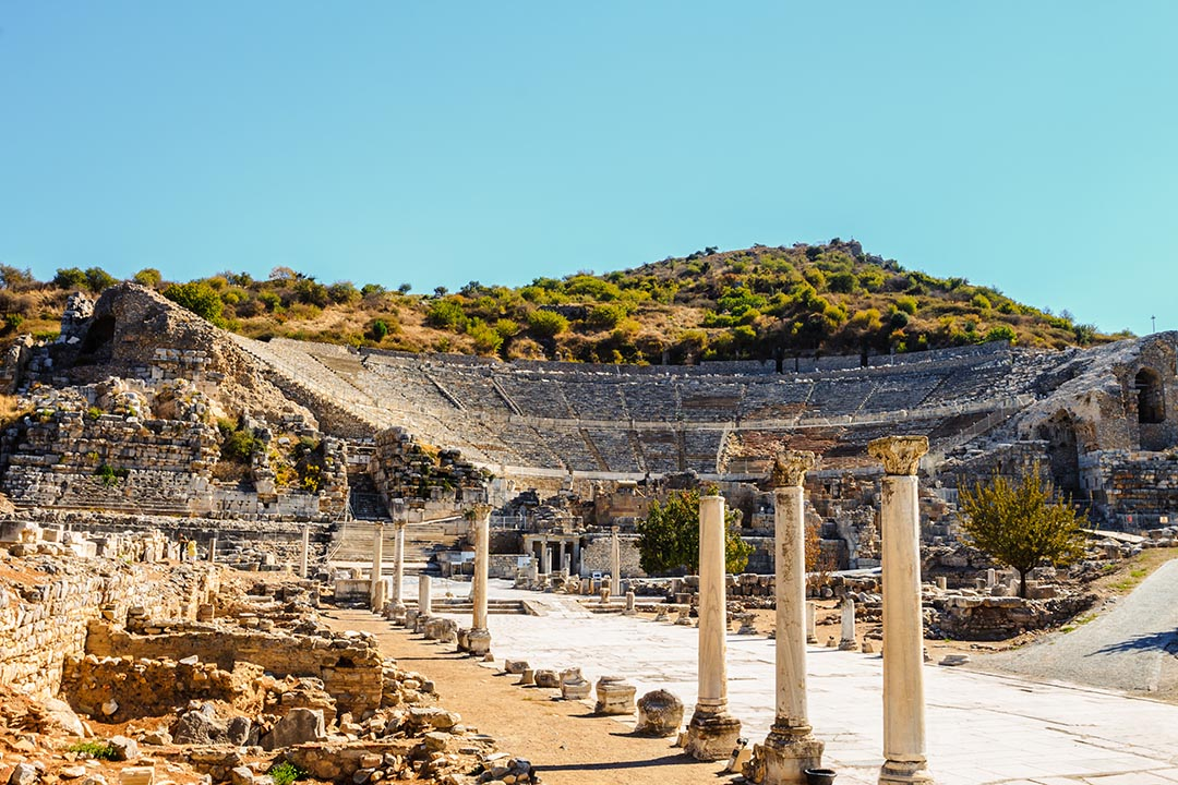 An ancient amphitheater in Ephesus with a big paved walkway lined by columns leading up to it. There are green trees behind the amphitheatre and blue skies.