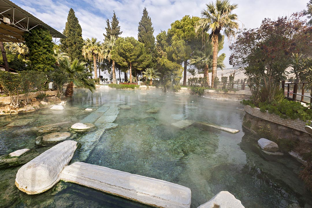A historical thermal pool in Pamukkale with blue steaming water and green trees in the background