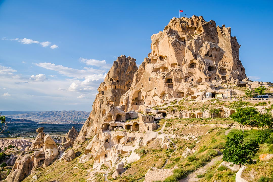The Uschisar Castle in Cappadocia carved out of the pale orange stone and looking over the landscape.