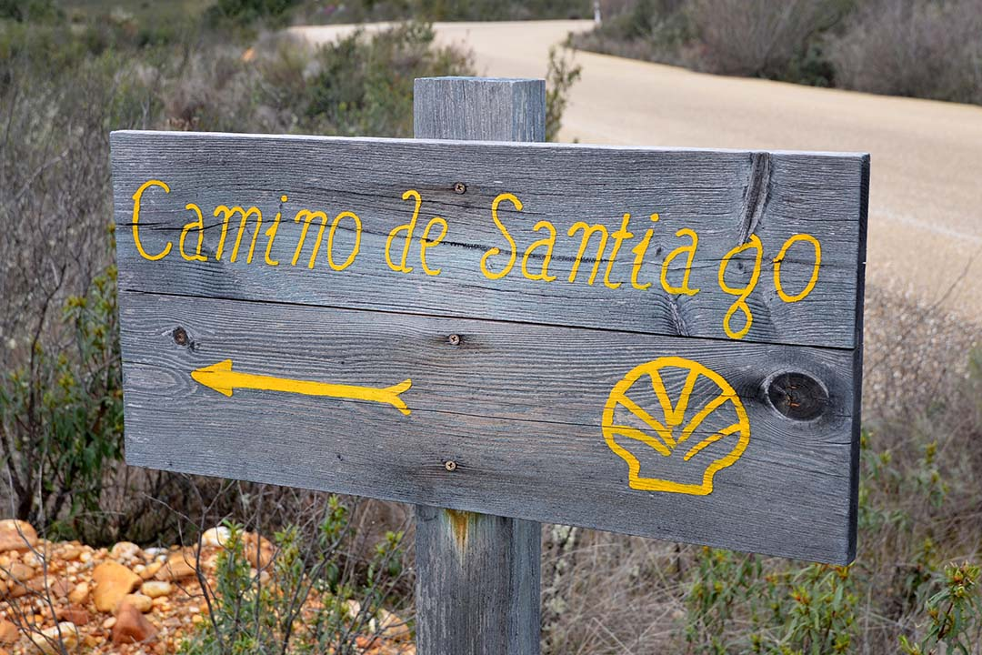A sign post with Camino de Santiago written on in yellow, with an arrow and shell drawn on
