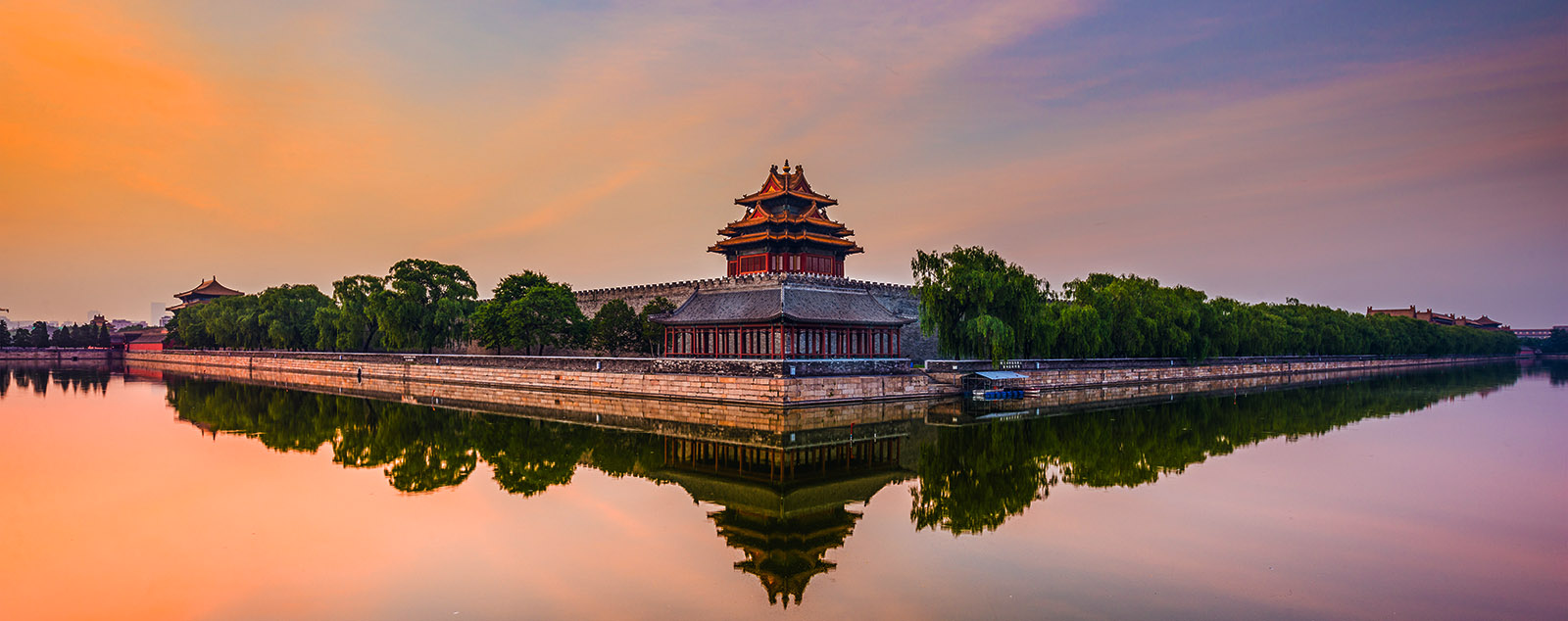 A corner tower of the Forbidden City's ramparts surrounded by a serene moat
