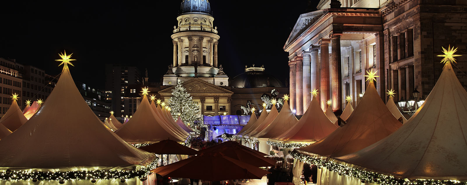 The tops of market stalls adorned with twinkling fairy lights