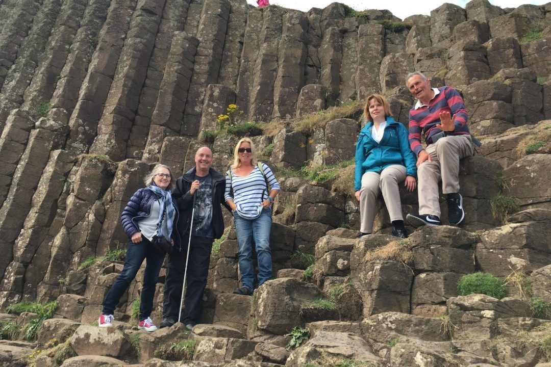 A group of travellers posing with their canes on the Giants Causeway