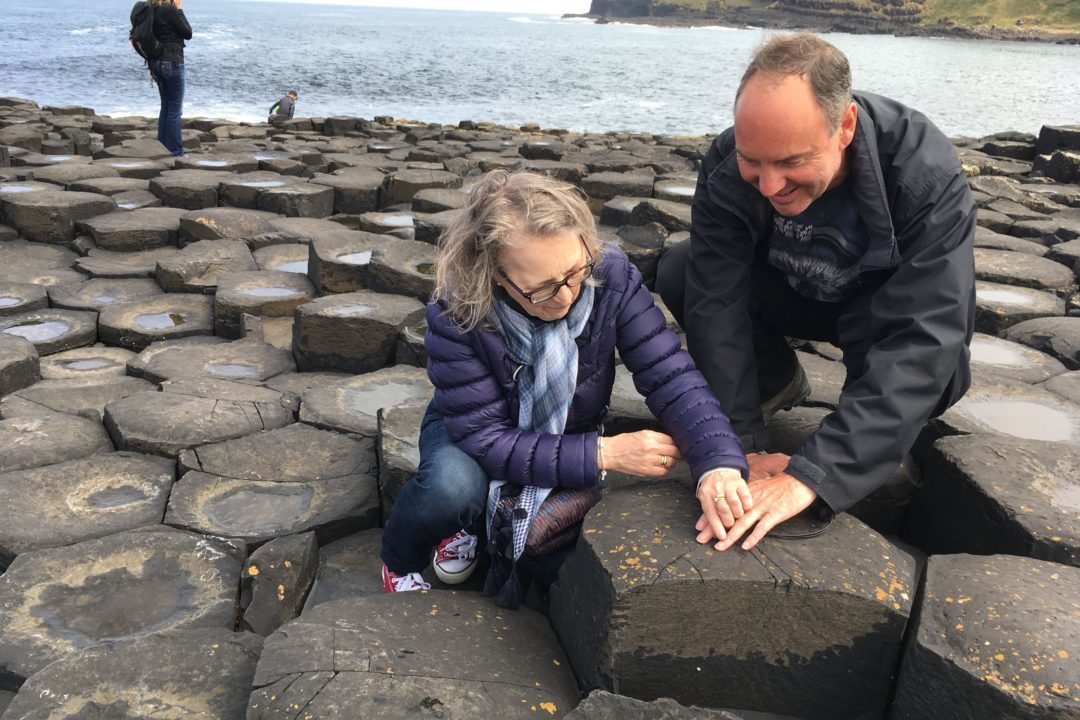 Two travellers kneel on the Giants Causeway to touch the rocky textures