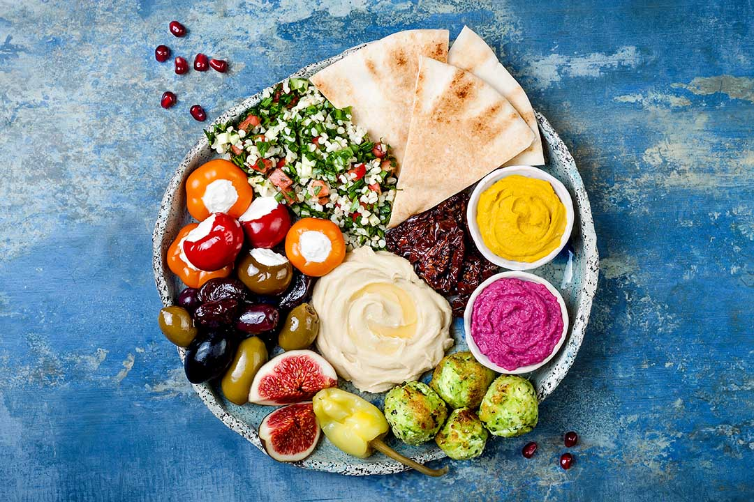 Middle Eastern meze platter with green falafel, pita, sun dried tomatoes, pumpkin and beet hummus, olives, stuffed peppers, tabbouleh, figs.