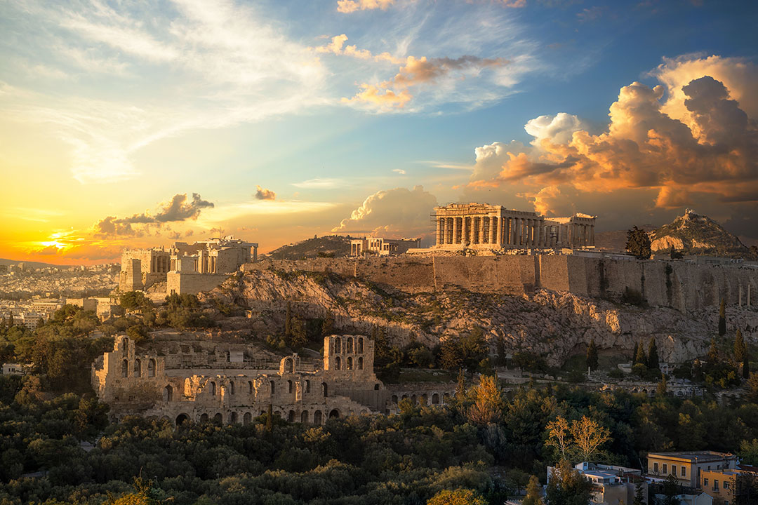 A view of the Acropolis of Athens under and orange sky