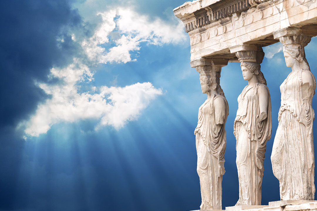 3 female statues stand as pillars for an ancient ruin, the sky is a bright blue