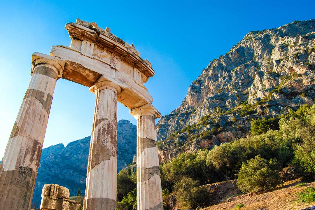A greek temple at the base of a mountain range
