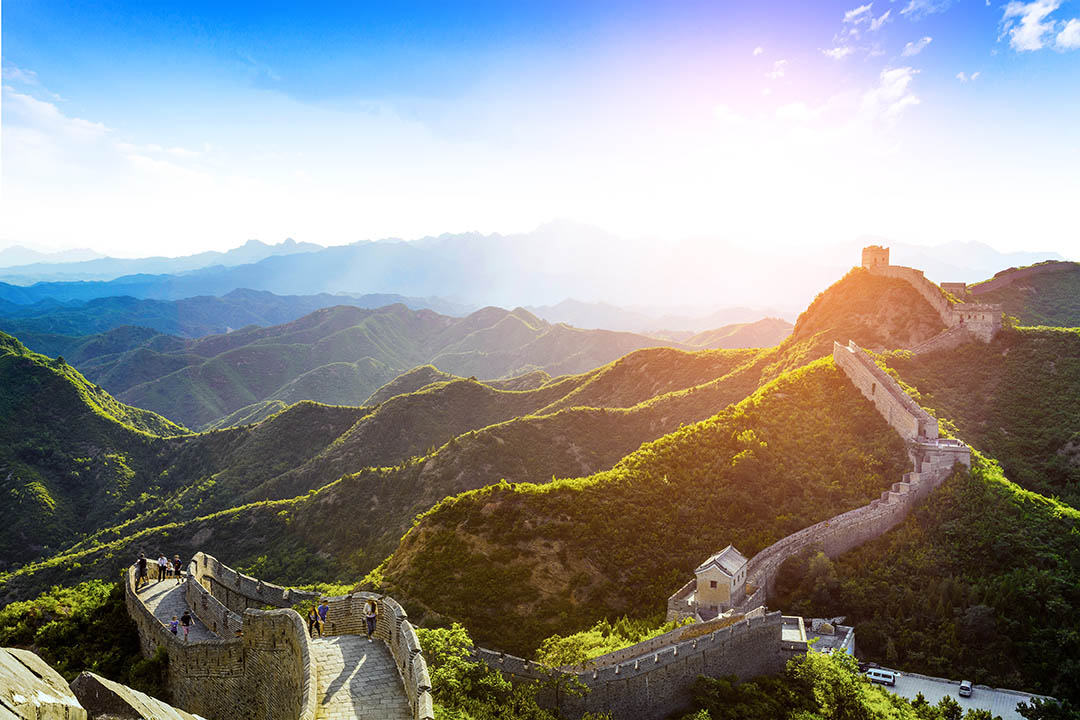 A view of the Great Wall of China, across the hills with a bright blue sky