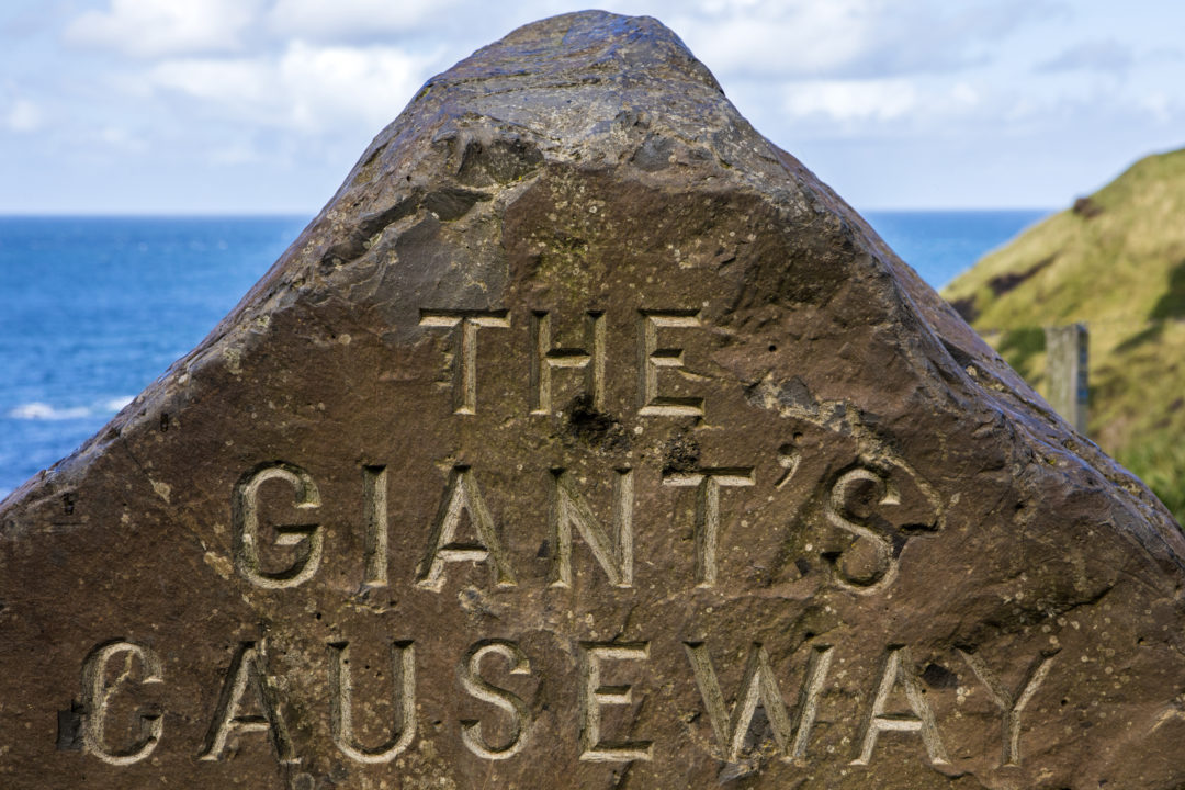 A sign for the Giants Causeway in Northern Ireland etched into a rock.