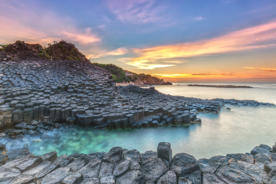 Sunrise on the Giants Causeway, illuminating the sky yellow