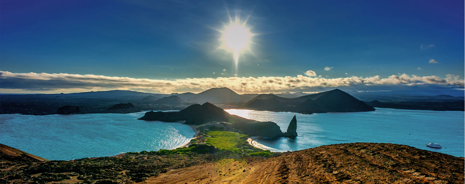 A view with the sun in the sky, blazing over some of the Galapagos islands, surrounded by blue waters