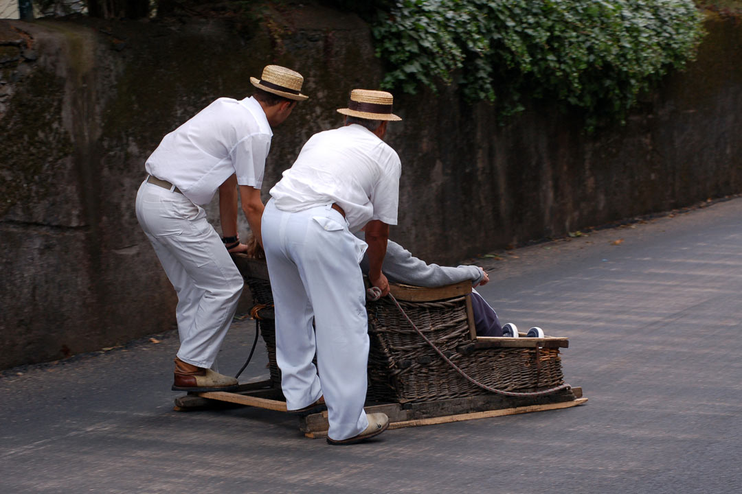 Locals pushing the famous toboggan down into Funchal