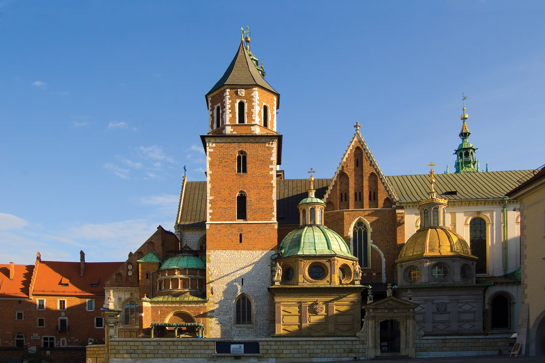 A medieval Polish church with green domes.