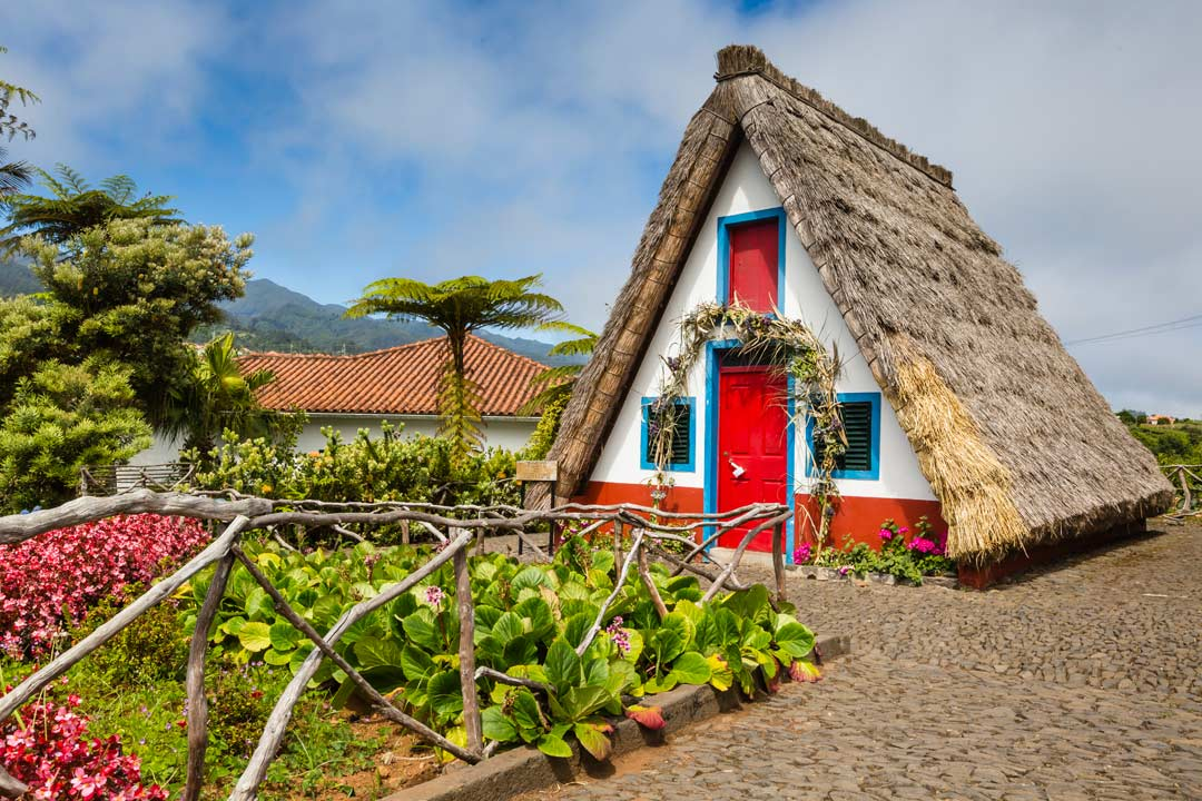 A traditional Madeiran building, painted white with red and blue trimmings with a thatched roof.