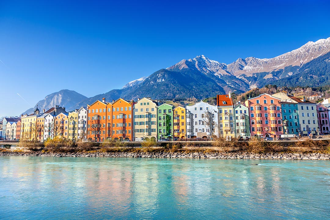 The brightly coloured houses of Innsbruck next to the water edge