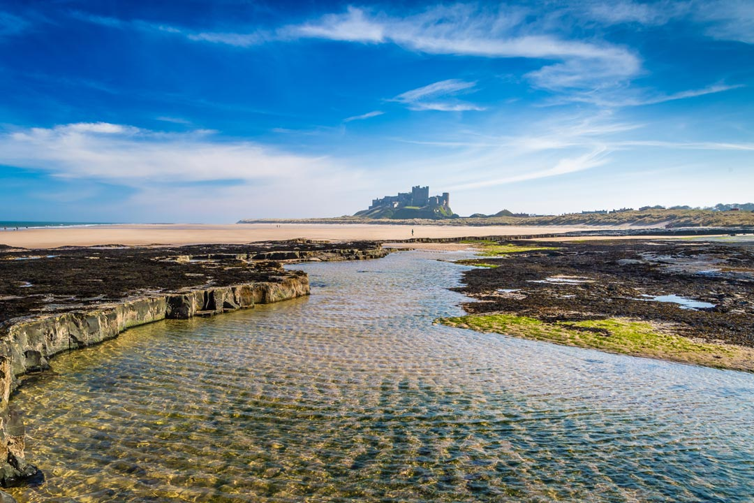 Bamburgh Castle stands atop its perch in the horizon, with the beach in the foreground