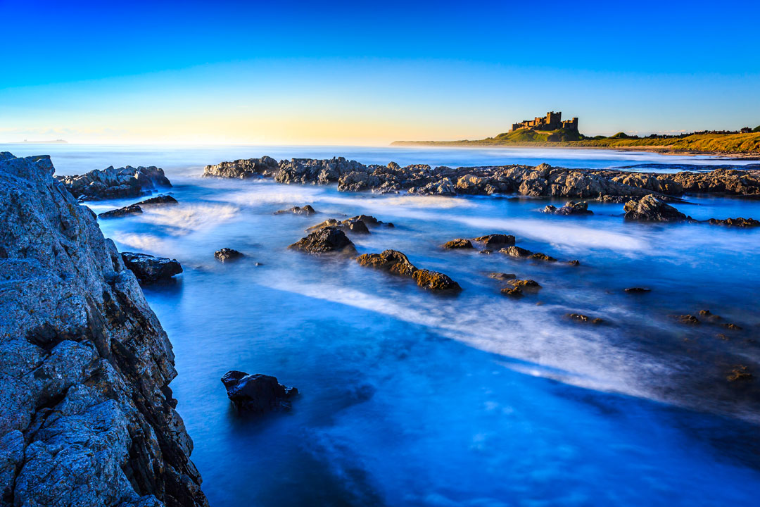 Vibrant blue waters and dark rocks in the foreground, with Bamburgh Castle visible in the background